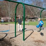 Heidi pushes Trey on a swing at Moccasin Creek State Park