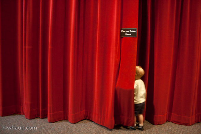 Trey looks behind the red curtain - no wizard, just the theater at the museum